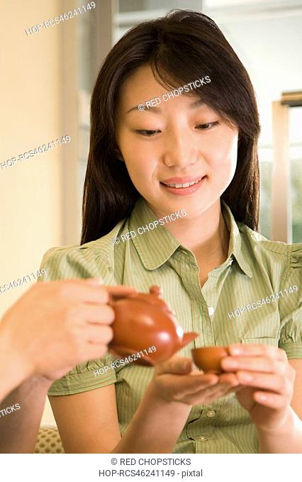 Close-up of a person's hands pouring tea into a cup held by a young woman