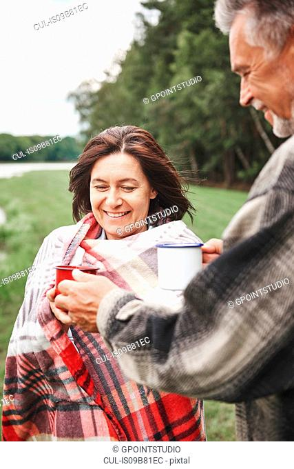 Mature couple standing in rural setting, holding hot drink, woman wrapped in blanket