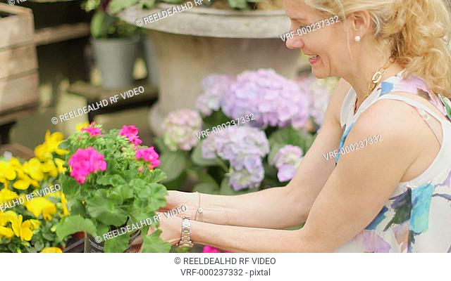 A woman crouches down outside a Florist's and takes a closer look at the array of indulging flowers