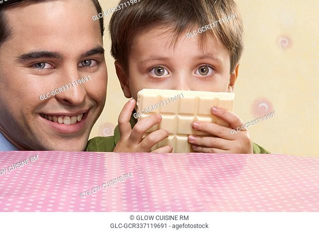 Portrait of man with his son holding a bar of white chocolate