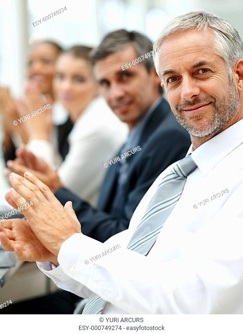 Portrait of successful business team applauding at a conference