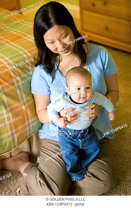 Elevated view of an Asian mother sitting on the floor holding an infant boy on her lap