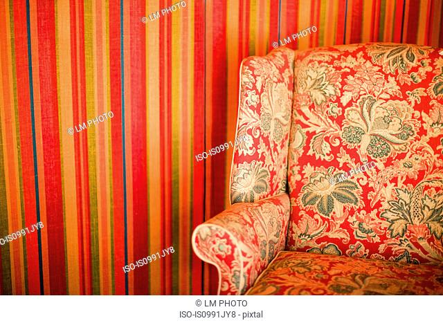 Floral patterned chair against striped wall