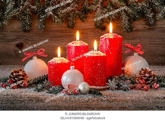 Natural Christmas decoration. Four red burning candles with christmas baubles and cones. Switzerland