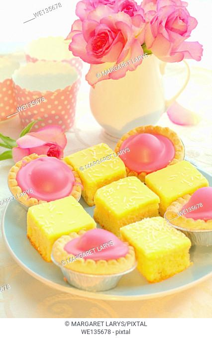 Beautiful colorful cakes and pink roses, still life