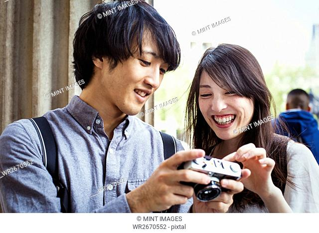 Young Japanese man and woman enjoying a day out in London, holding at a digital camera, smiling