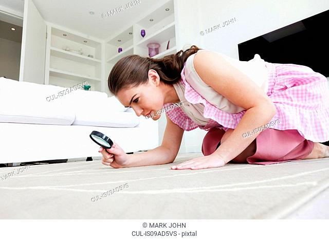 Young woman on hands and knees inspecting rug with magnifying glass