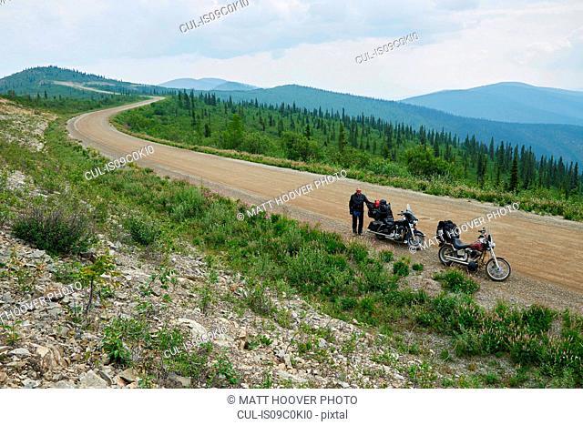 Senior male motorcyclist on rural mountain roadside with motorbike, high angle portrait, Dawson Creek, Canada