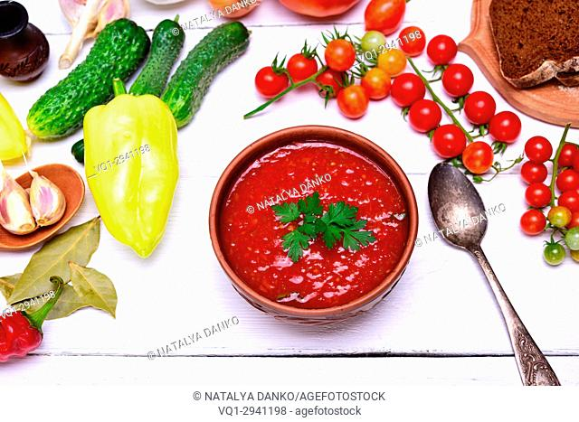 thick soup of tomato and vegetables gazpacho in a brown round plate on a white table