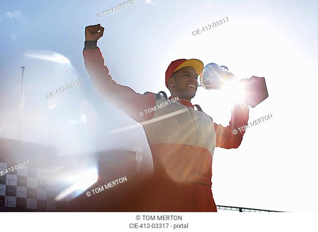 Cheering racer holding trophy on track