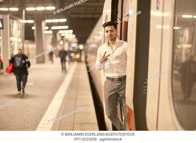 young man in door of train, at train station, showing peace sign, in Munich, Germany