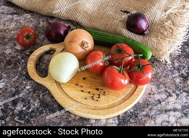 Fresh vegetables - onions, tomatoes, cucumber on a cutting board