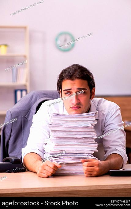 Male employee unhappy with excessive work in the office
