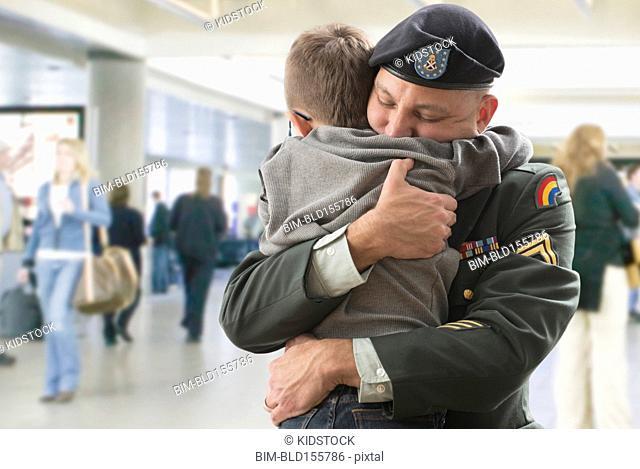 Caucasian returning soldier hugging son in airport