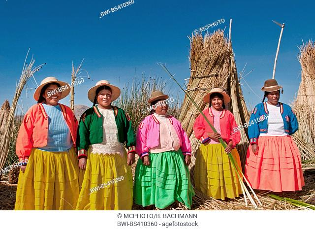 women of the Uros in traditional clothing on a swimming reed island, Uros at the totora harvesting, Peru, Andes