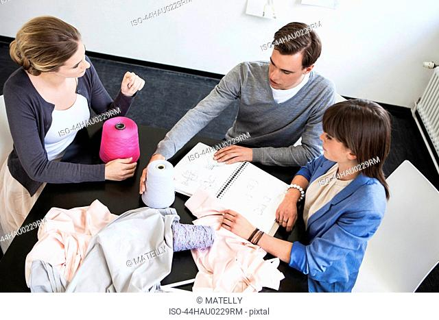 Business people examining fabric