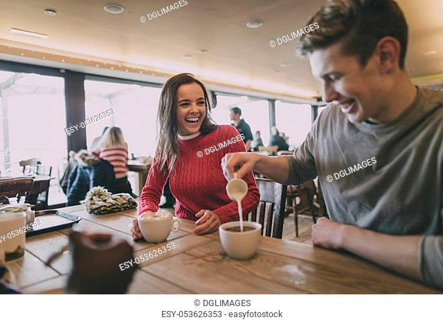 A young couple laugh in a cafe in winter whilst the male pours milk into a cup of coffee