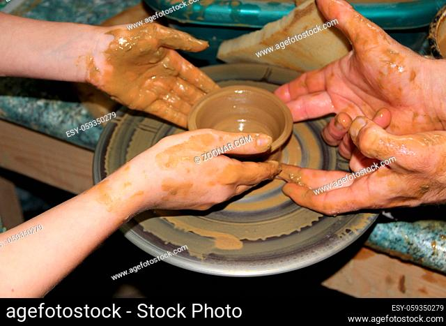 Pottery making process. Ceramic from clay. Art of pottery. Master class from clay on potter's wheel. Hands of potters creating earthen jar on the circle
