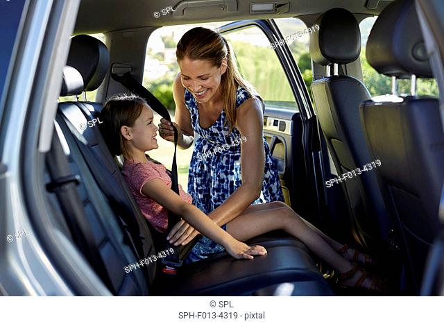 MODEL RELEASED. Mother putting on daughter's seat bet in the back of the car