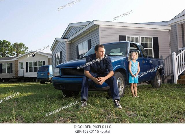 Blue-collar man sitting on old truck in front of trailer home with daughter