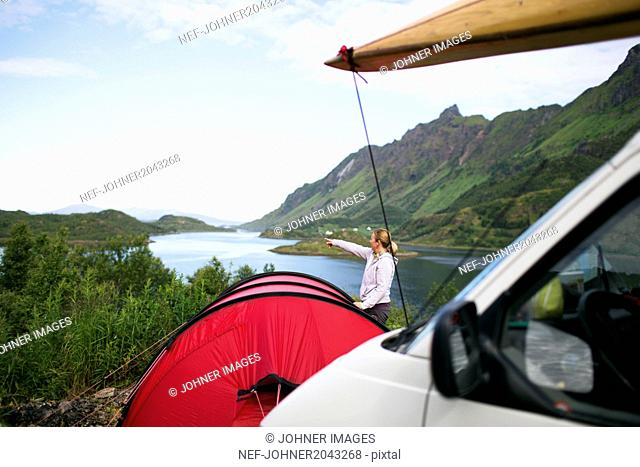 Van parked near tent, woman looking at view