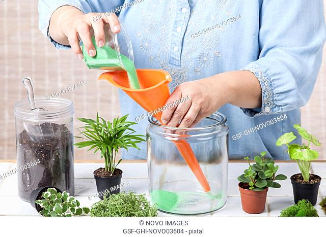 Woman Pouring Green Sand into a Terrarium Vessel using a Long-Nosed Funnel