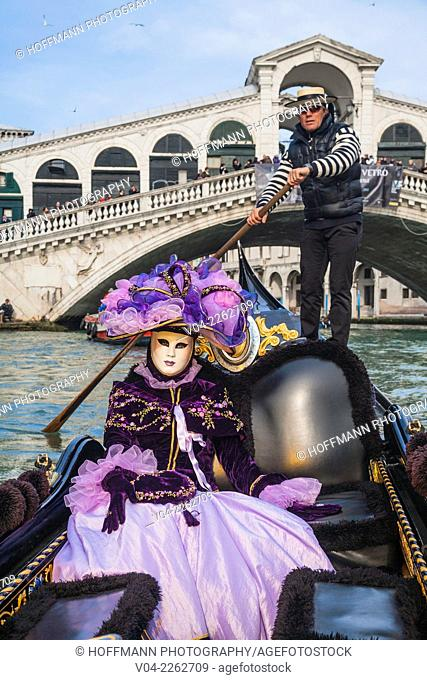 A masked woman in a gondola in front of the Rialto Bridge at the carnival in Venice, Italy, Europe