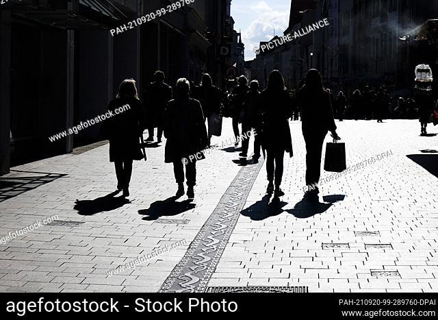 20 September 2021, Schleswig-Holstein, Flensburg: People walk through Flensburg's city centre with shopping bags. Since September 20, 2021