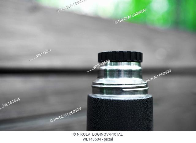 Horizontal black and white thermos with green bokeh background