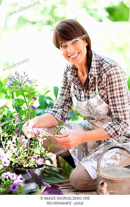 Woman examining plants in garden