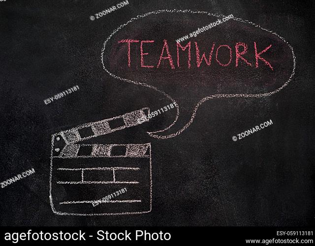 Open movie clapper and speech bubble with teamwork word drawn with chalk on blackboard