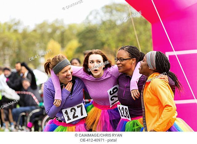 Happy female runners hugging at charity run finish line