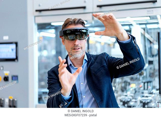 Businessman wearing AR glasses in a modern factory
