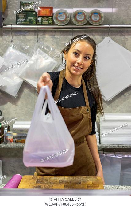 Female butcher giving plastic bag