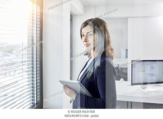 Smiling young businesswoman with tablet looking out of window in office