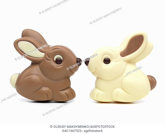 Two cute milk and white chocolate bunnies sitting nose to nose isolated on white background