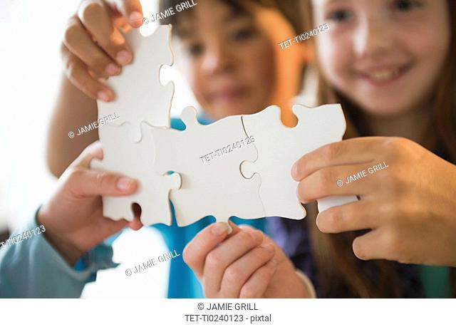 Close up of children's 8-9 hands holding jigsaw pieces