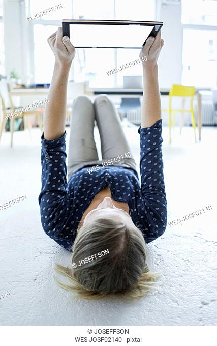 Young woman lying on the floor in a loft holding tablet