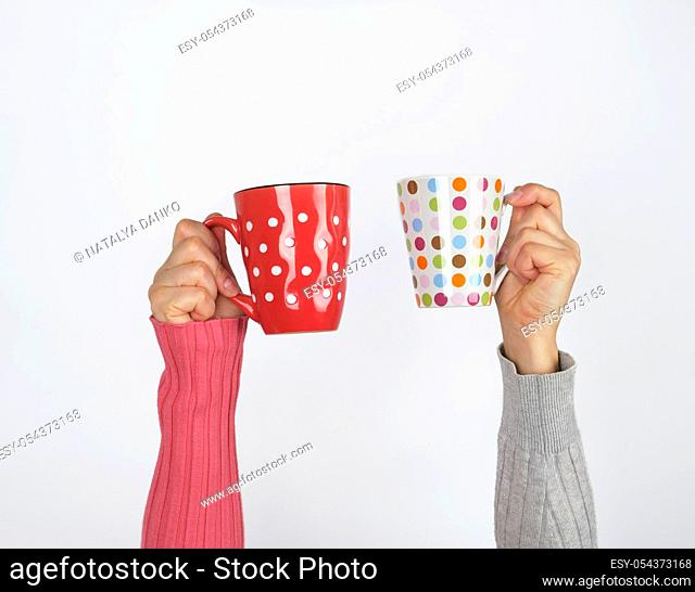 two hands holding ceramic mugs on a white background, copy space, coffee time