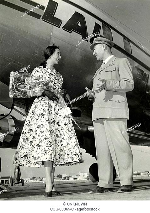 A woman wearing a flowered dress next to a pilot of plane on the runway, Italy