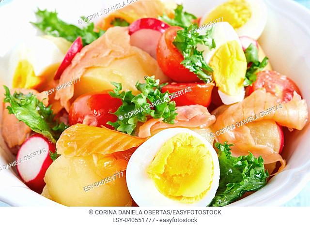 Closeup of bowl with salad of mixed ingredients: boiled potatoes and eggs, smoked salmon, cherry tomatoes, lettuce and red radish