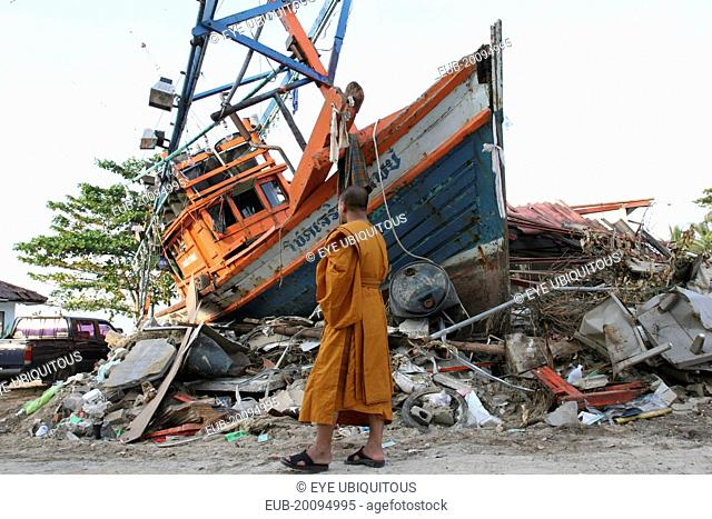 Tsunami. Monk looks at the damage caused by the tsunami, nothing is left standing in the village 2500 people are pressumed dead