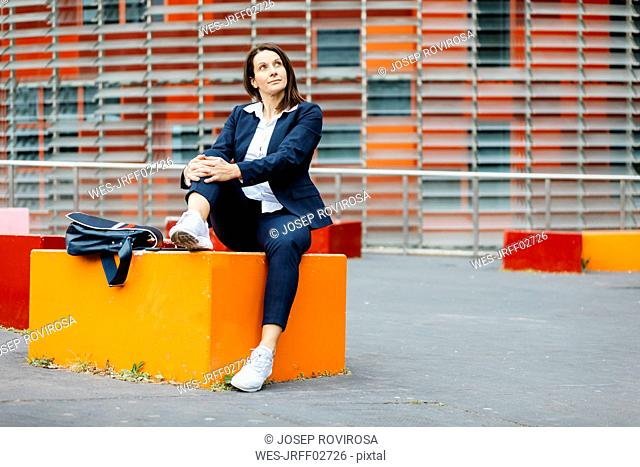 Businesswoman sitting outside office building in the city