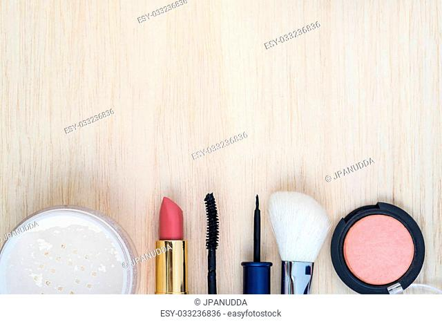 Woman earth tone cosmetics (makeup) - mascara, eye liner, brush on, lipstick, powder, brush on wood background. Top view with space for text