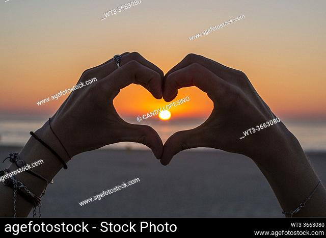 Girlâ. . s hands making a heart that surrounds the Sun at sunset