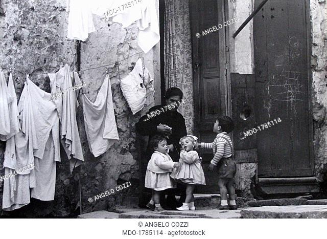 Woman hanged out the washing. A grandmother has just finished to hang out the washing in company of her grandchildren. Castellammare del Golfo, 1950s