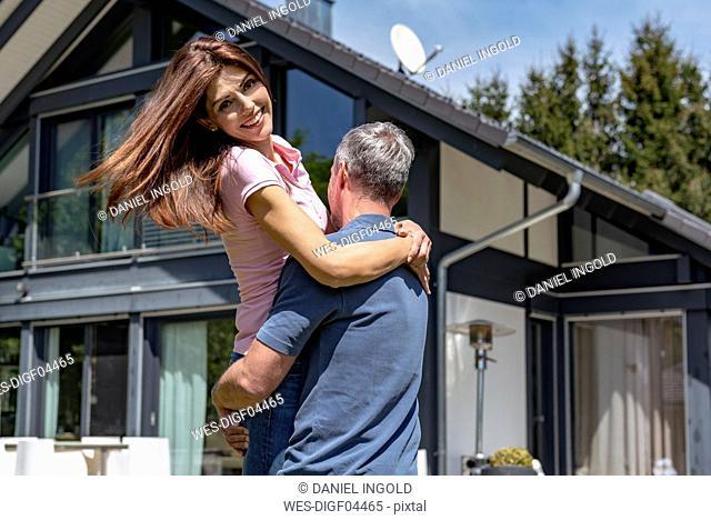 Happy couple having fun in garden of their home