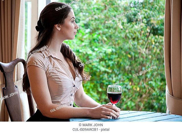 Young woman sitting at table in front of window holding glass of wine looking away