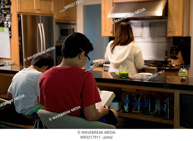 Kids reading book while mother preparing in kitchen