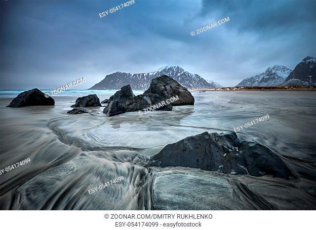 Rocks on Norwegian sea beach in fjord. Skagsanden beach, Flakstad, Lofoten islands, Norway. Long exposure motion blur